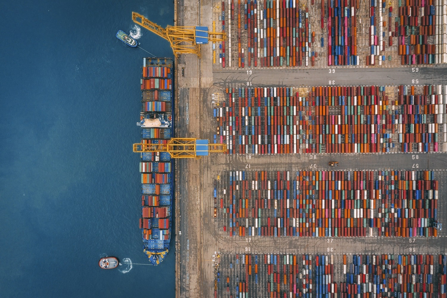 Aerial view of business port with Shore crane loading containers in freight ship.