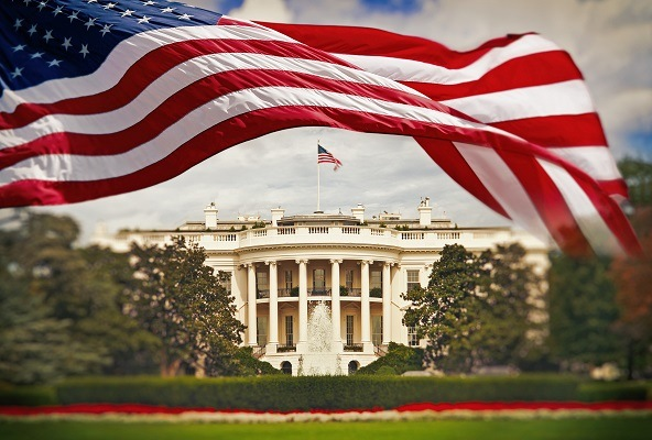 The White House in Washington DC with waving United States flag