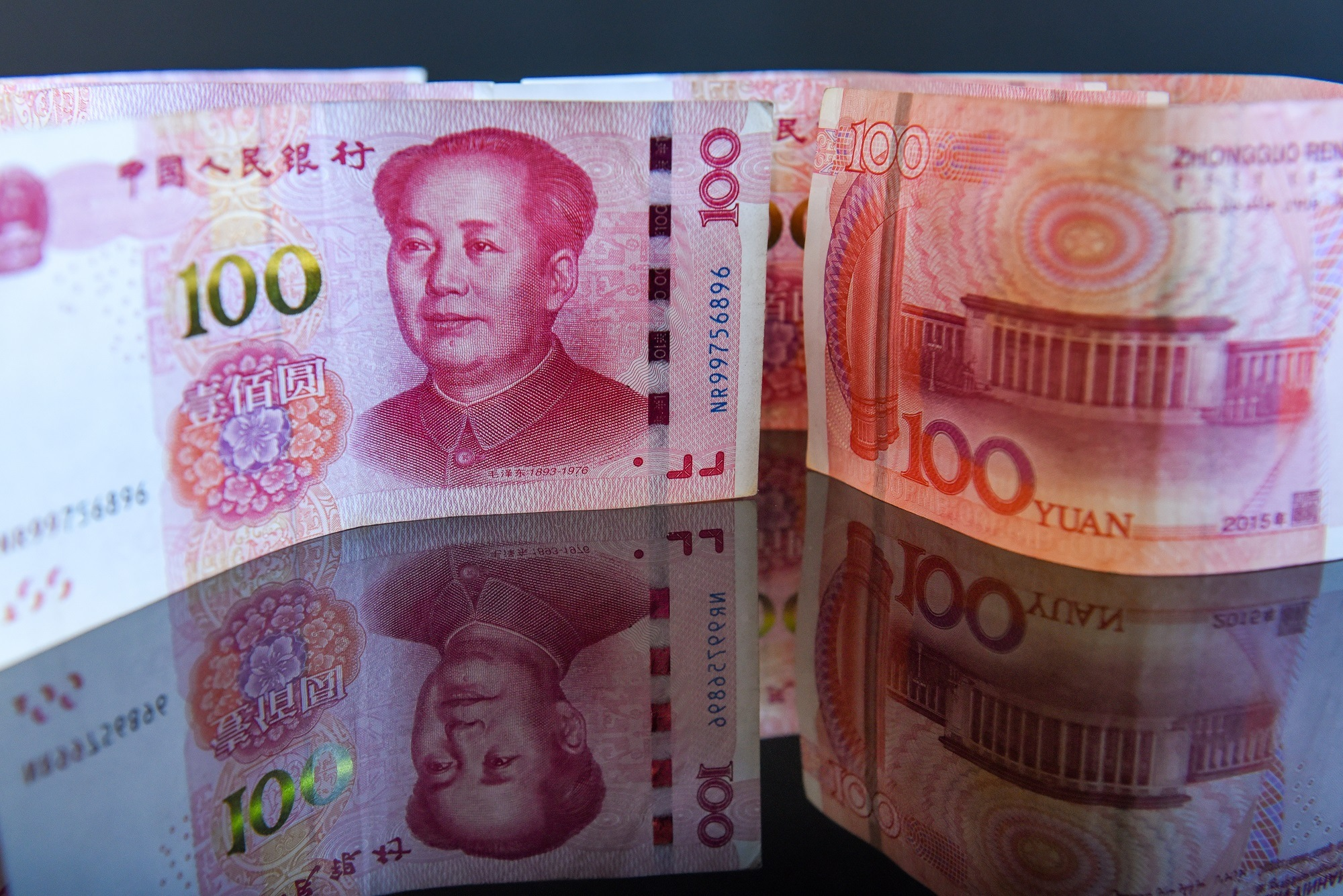 Indoor shoot of Chinese currency - Yuan. No people on the pictures, just different arrangements of the bill of 100 (one hundred) yuan placed on a reflective surface. Good for illustration of tariffs negotiations between China and USA