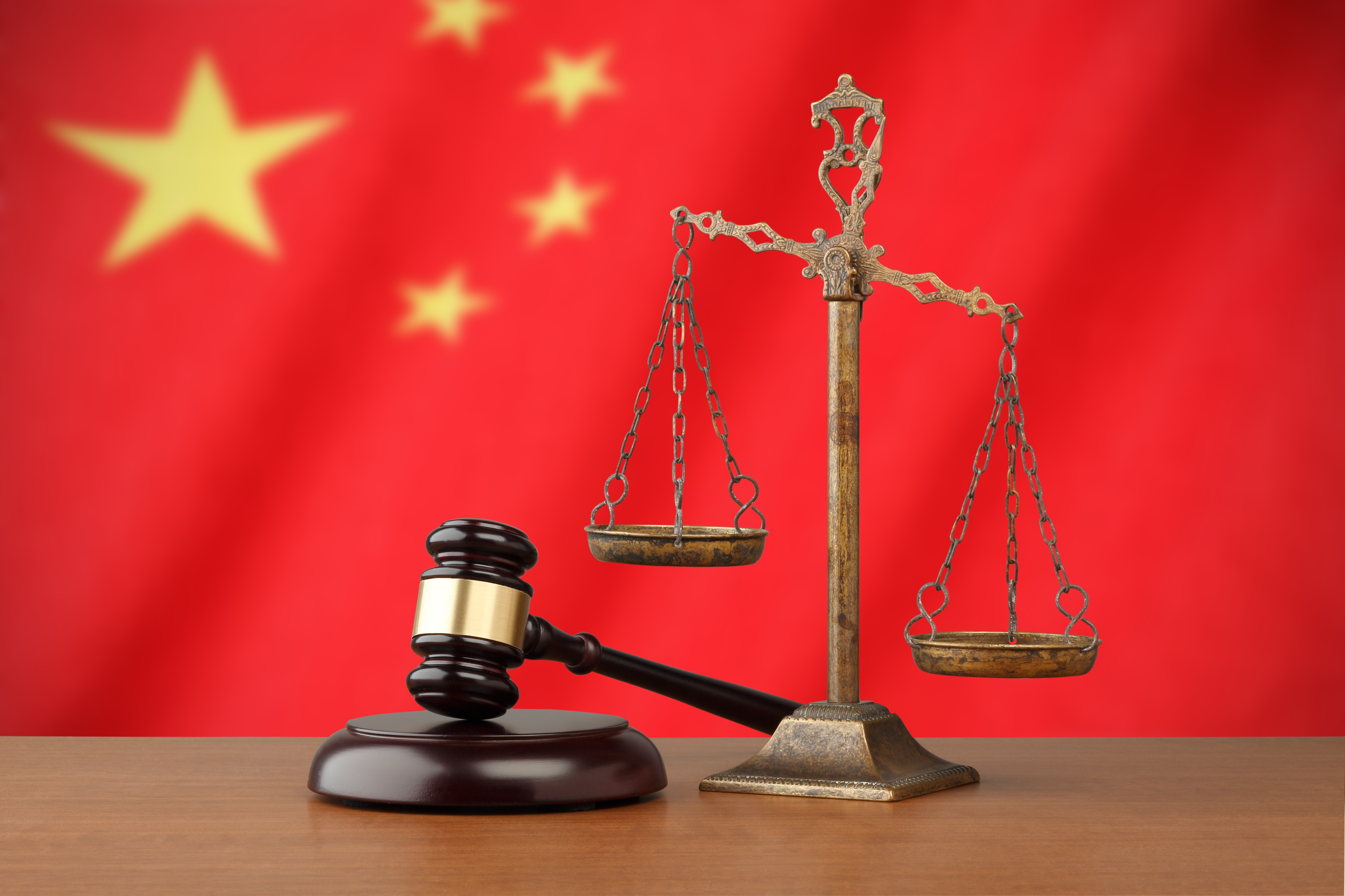 Chinese flag and golden scale with a judge's gavel