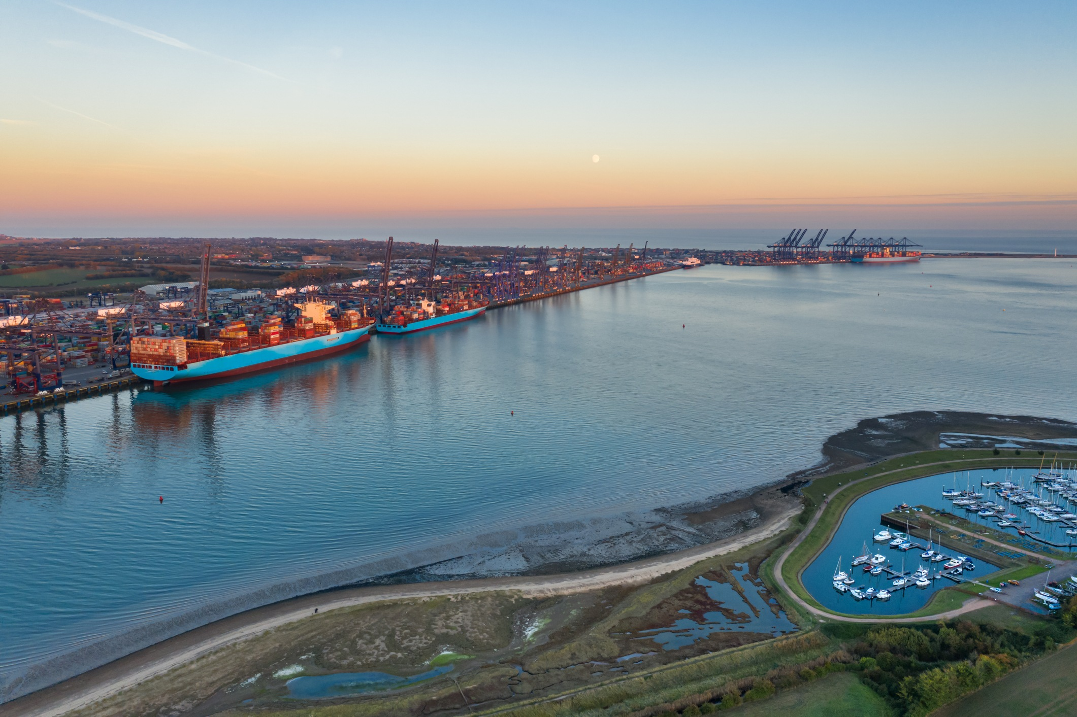 Sunset and moonrise over Felixstowe container port shot from a drone over Shotley Gate, Suffolk, United Kingdom