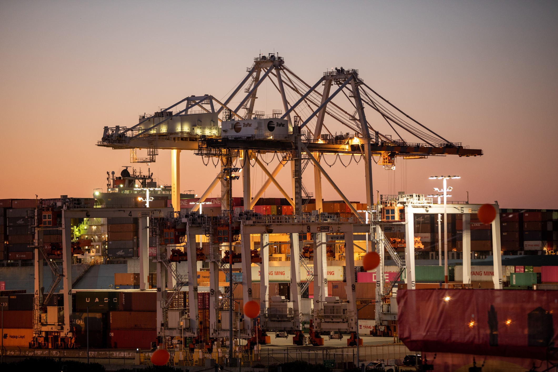 A dusk view of the shipping containers and longshoreman equipment at the Port of Oakland