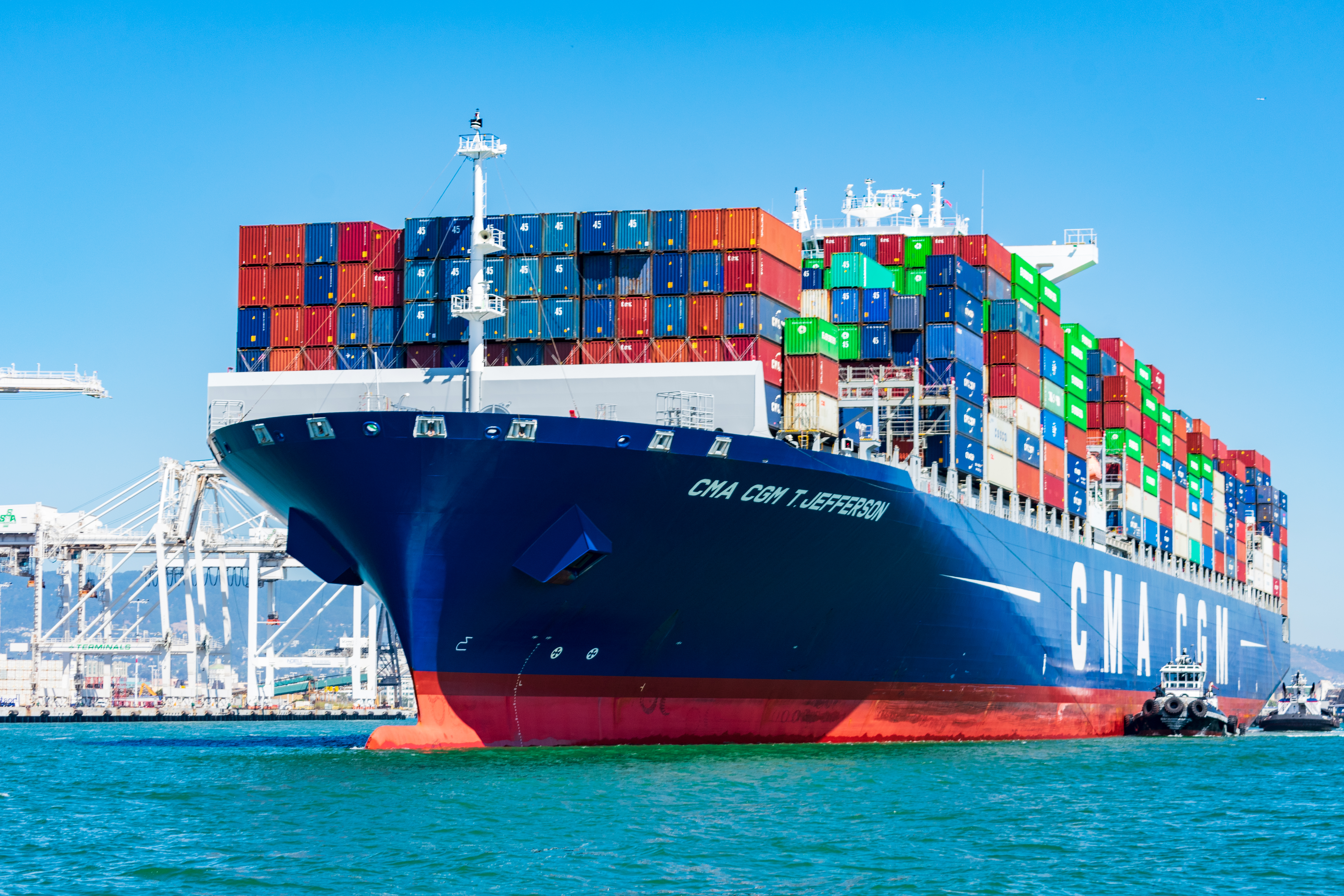 Oakland, California, USA - August 30, 2019 : Tugboats assist French container ship CMA CGM at the Port of Oakland under blue sky. A tugboat maneuvers vessel by pushing, pulling or towing containership