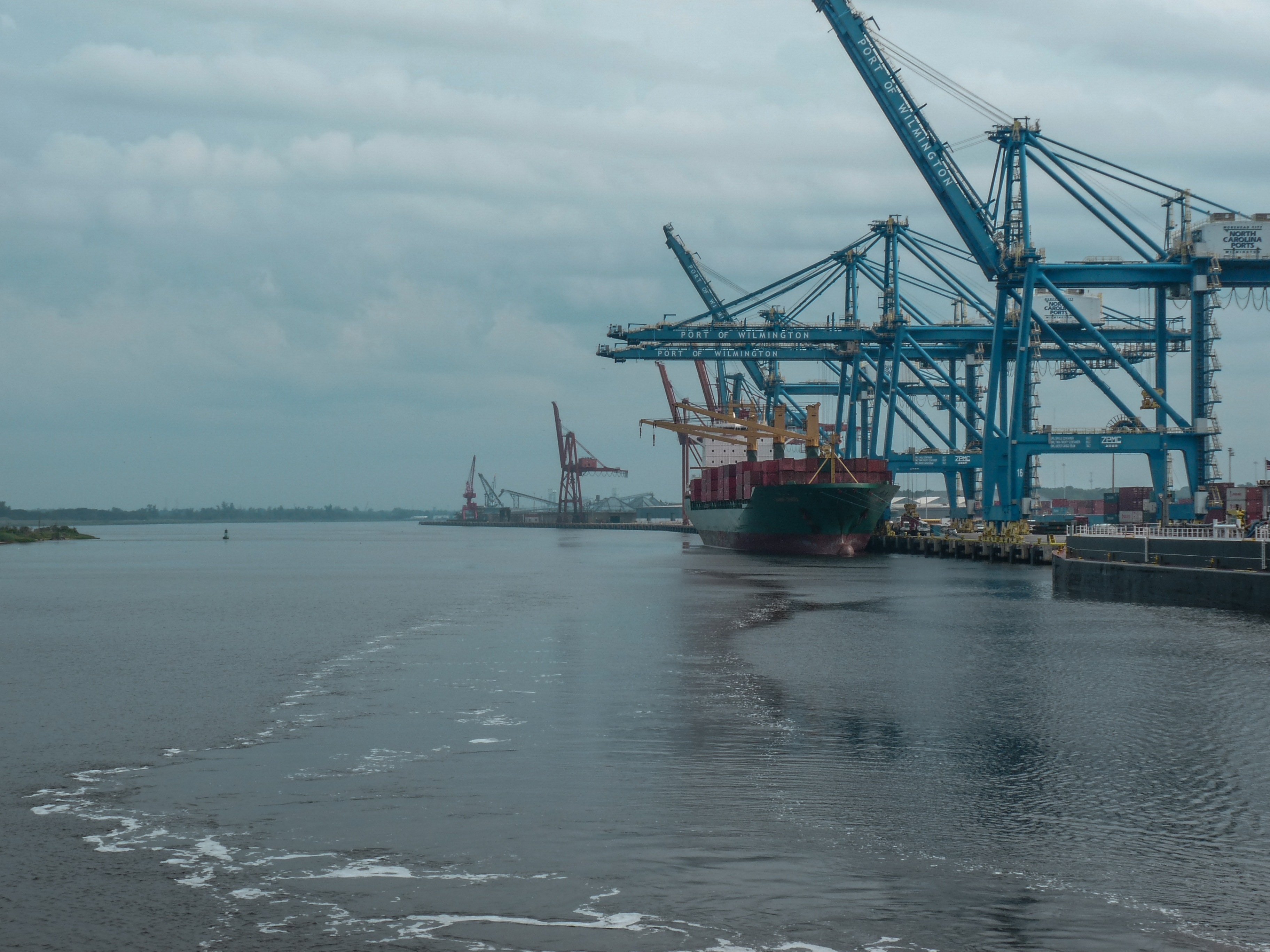 From the deck of the Henrietta II approaching the seaport at Wilmington, NC with view of cranes, docks and and ocean going container ship unloading cargo