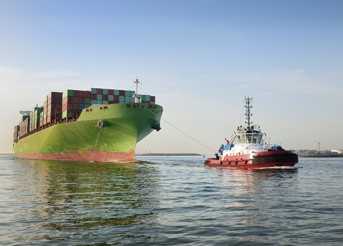 front view on a tugboat towing a large cargo container ship with piled up cargo containers on deck into harbor.