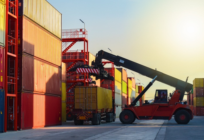 Container logistics, quay crane load and unload cargo container from vessel. Port operations. Forty feet container hang up in the sky with yellow sunlight background.Reach stacker unload container from truck in container yards, Logistics operations.