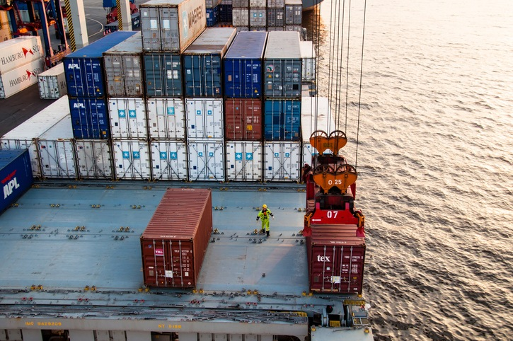 Hamburg, Germany - May 10, 2011: A worker is assisting the uploading of containers on a container ship at a dock at the Container Terminal Altenwerder in Hamburg, Germany.