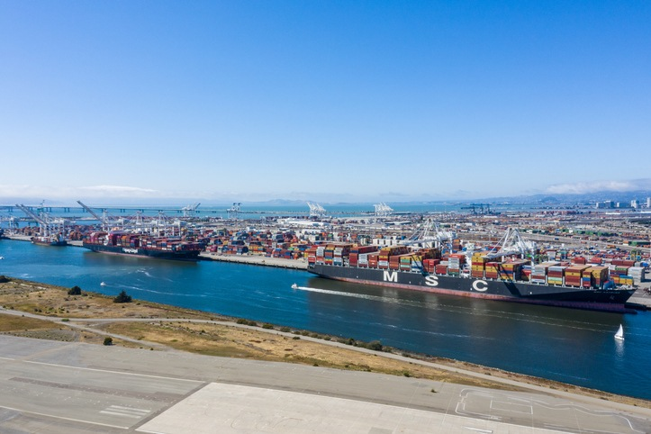 Aerial view of containers and container ships in the Oakland port. Ships docked in the Oakland Estuary on a sunny day. Contaners as far as the eye can see.