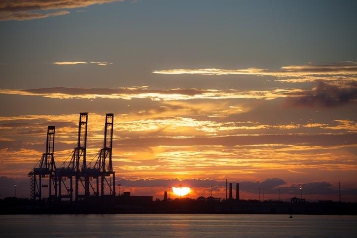 An incredible sunset backlights the shipping cranes at the port of Charleston, South Carolina