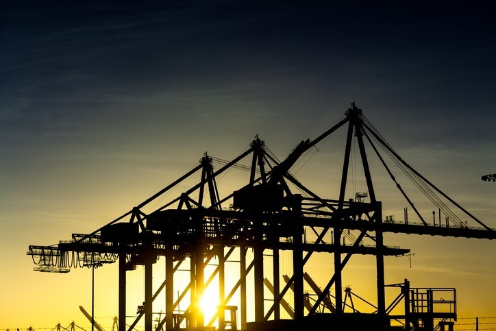 Cargo container unloading cranes at the dual port of Los Angeles and Long Beach, silhouetted by the setting sun