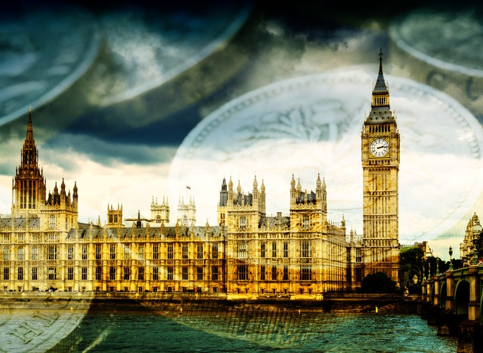 Famous London Tourist attraction Big Ben and the Houses of Parliament in England, with stacks of English Pound coins. Concept image suggesting money and government finances.
