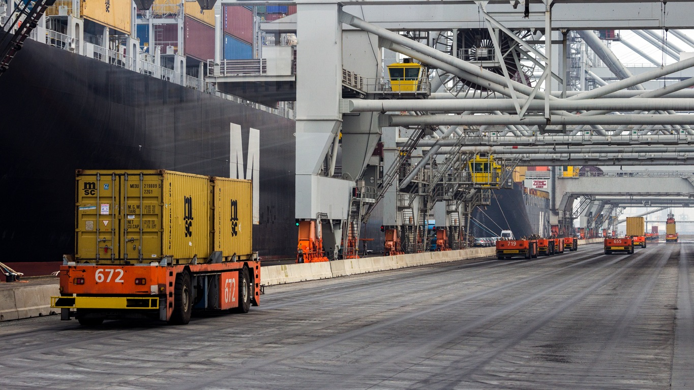 ROTTERDAM, SEP 6, 2013: Automated Guided Vehicles moving shipping containers to and from gantry cranes in a port container terminal.