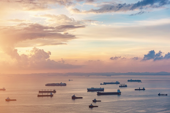 Aerial view of freight transportation ships, container ships and industrial boats at beautiful sunrise twilight light to the horizon close to singapore city transportation hub harbor. Singapore Strait, Singapore, Asia.