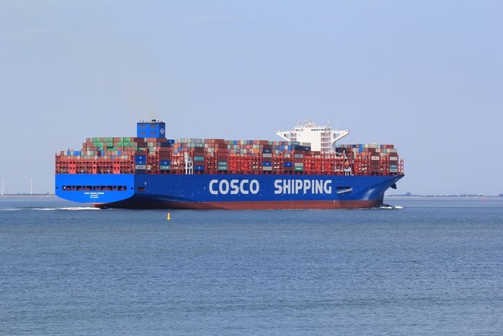 large blue new container ship cosco shipping macro navigates through river scheldt with high tide towards antwerp in summer