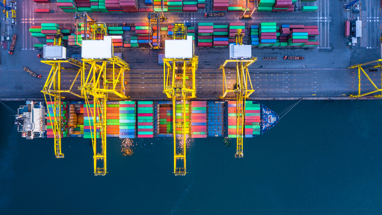 Aerial view container ship with crane port loading and unloading container box at industrial port at night.