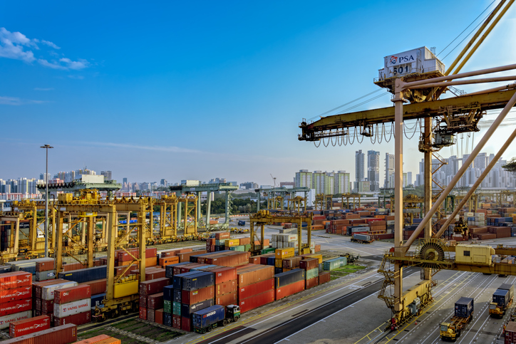 Singapore: Sunset panorama of Port of Singapore container cargo terminal, run by PSA, one of the busiest shipping terminals in the world. Keppel Harbour, Singapore, Malaysia.