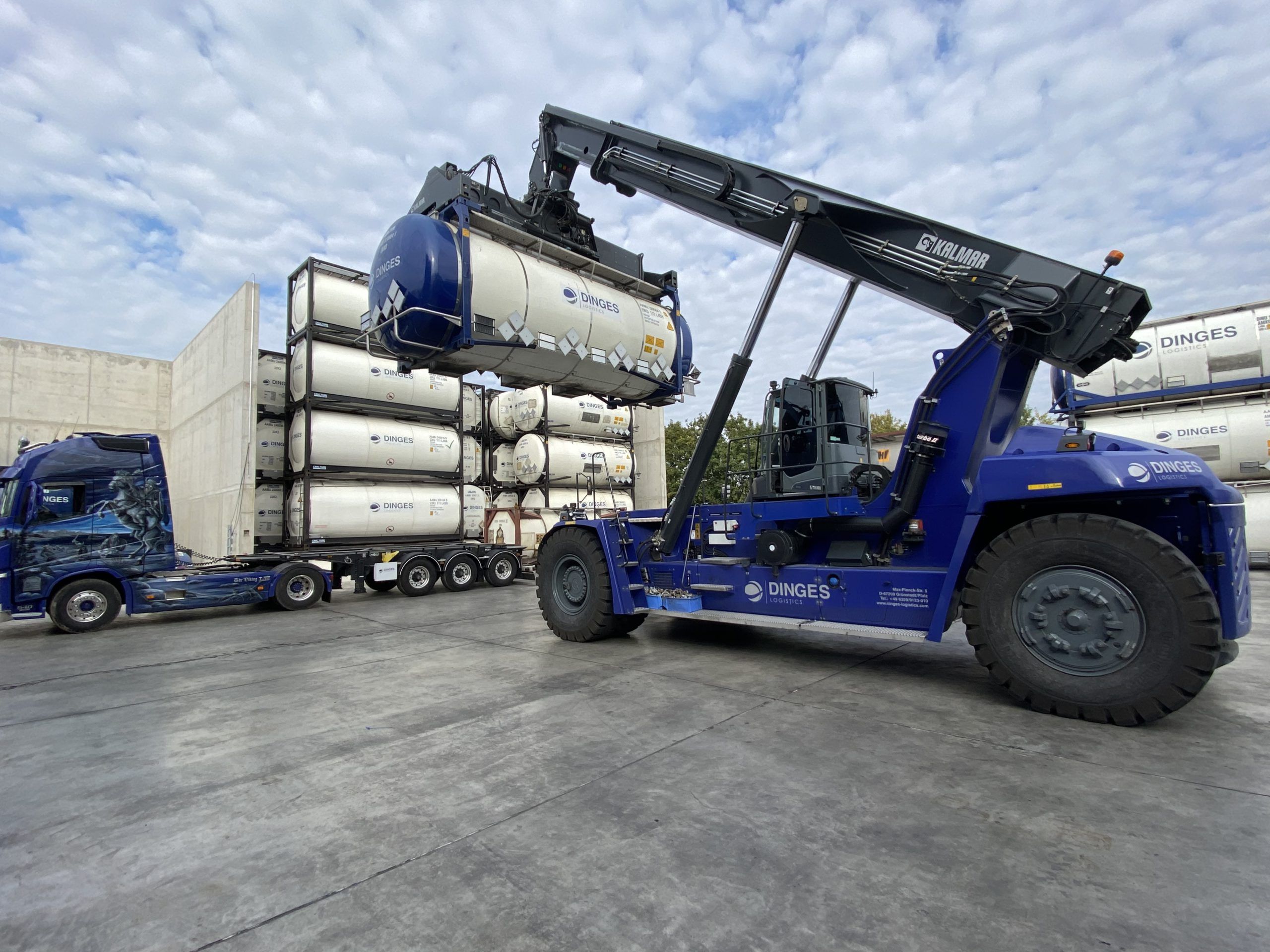 Blue reach stacker moving large white barrels onto a stack of barrels