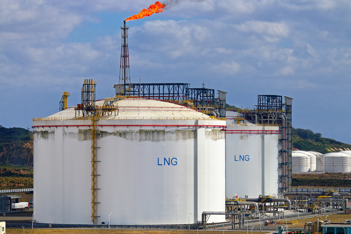 Picture of large LNG (Liquefied natural gas) tanks at LNG regasification terminal, with gas flare stack