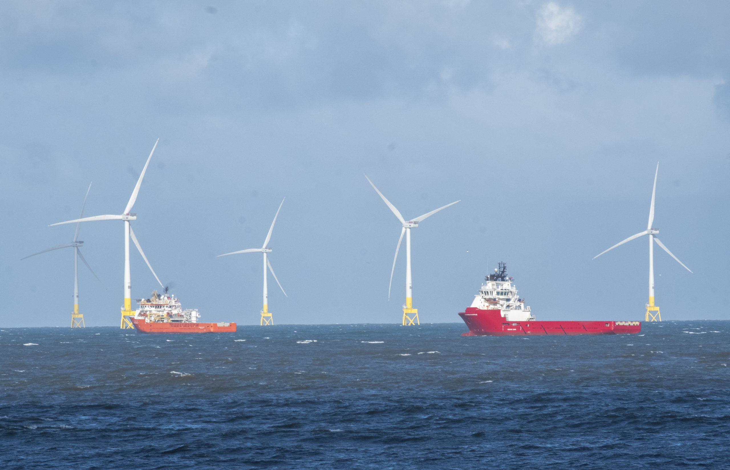 A group of tall offshore wind turbines in the North Sea, with cargo ships alongside them. These energy producing turbines are located off coastline of Aberdeen, on the east coast of Scotland. The renewable energy producers are an alternative to fossil fuel production, in an attempt to reduce the long term impact on our environment. They show a changing seascape along certain areas of the UK coastline, with shipping having to navigate around the manmade structures.