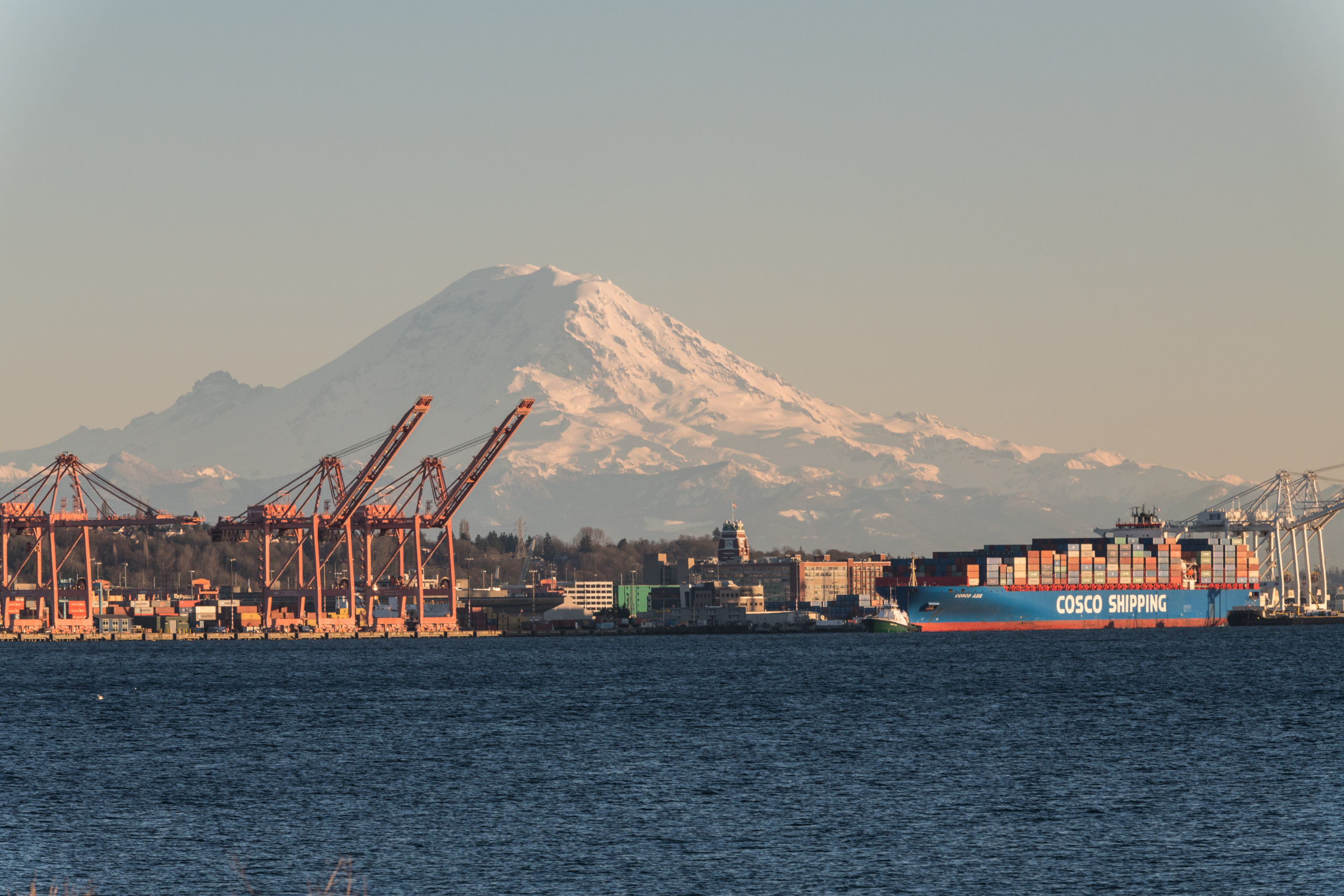 Seattle, USA - Mar 4, 2019: A Cosco shipping tanker on Elliott bay leaving port late in the day with Mount Rainier in the background.