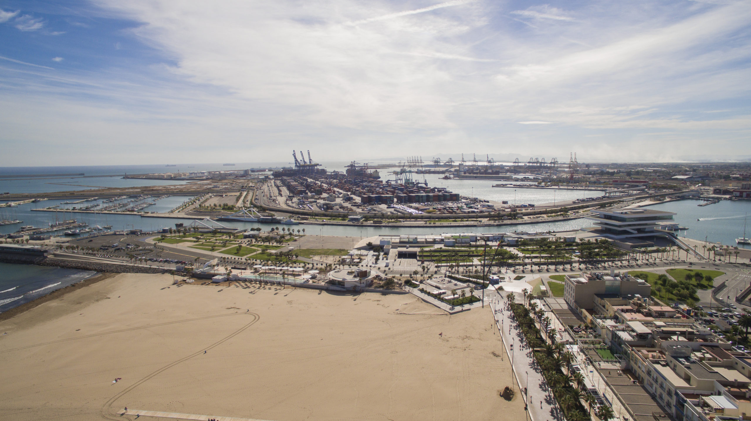 High angle view of harbor amidst sea. Buildings in Valencia on sunny day. Scenic view of sky over city.