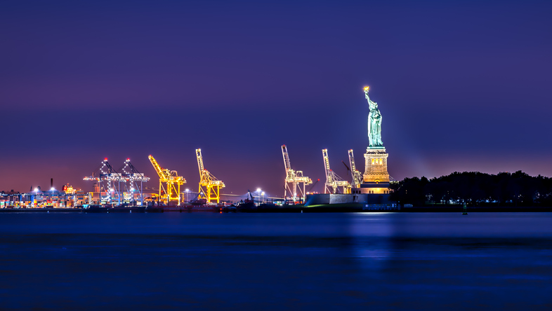 Statue of Liberty at dawn overlooking shipping docks and crane business.