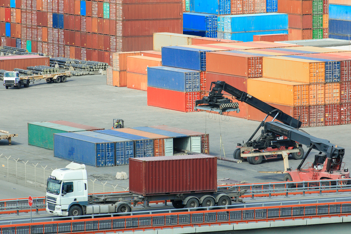 Forklifts  loads   containers at container terminal. Logistics import export background and transport industry of forklift handling container box loading at seaport. Export import goods.