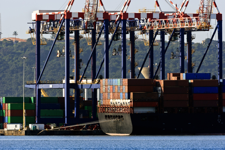 The stern of a container ship at the wharf with cranes.Here are similar images.