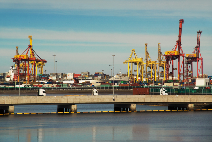 Sydney, Australia - April 29, 2014: Three trucks cross a bridge, before large cranes moving containers at Port Botany.