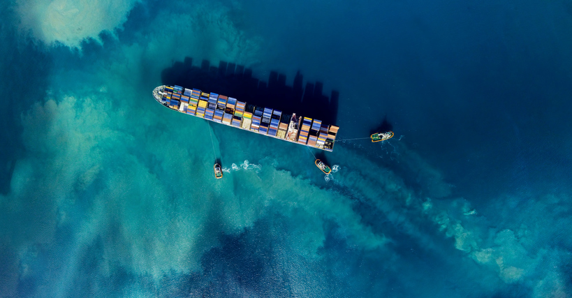 Aerial shoot of a cargo ship mooring in a harbour