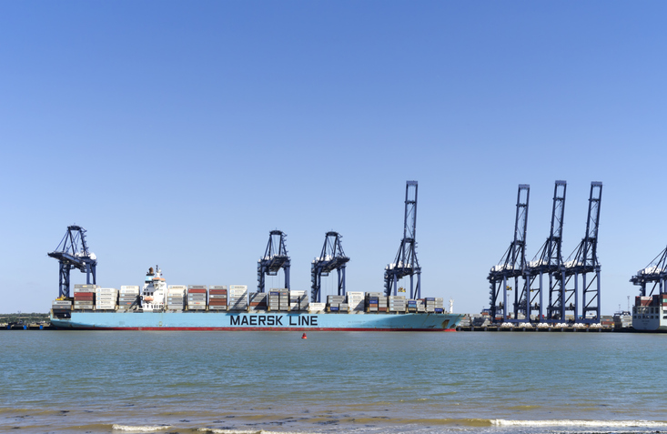 Felixstowe, England - August 31, 2013: A large Maersk Line container ship, the Maersk Klaipeda, stacked with containers at Felixstowe, Suffolk, in eastern England. Maersk Line is part of a large Danish company and is one of the largest container shipping companies in the world. The Port of Felixstowe is situated on the River Orwell estuary which leads to the North Sea.