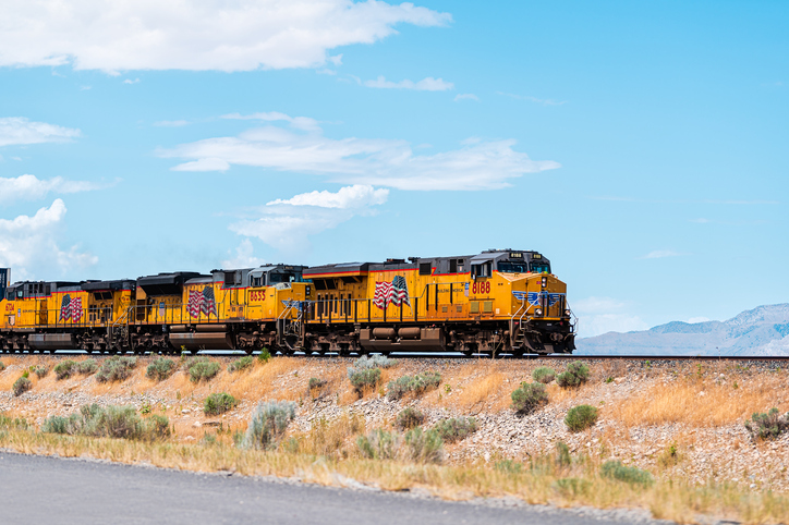 Salt Lake City, USA - July 27, 2019: Utah landscape with train on railroad with cars containers, and american flag on yellow color locomotive with mountains in desert background